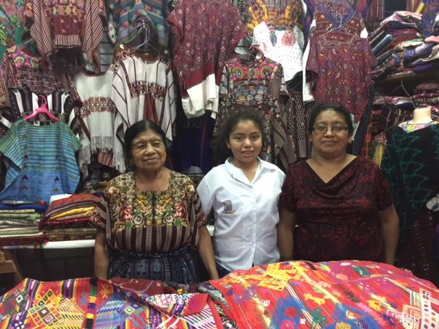 3 generations in huipile store. Panajachel, Guatemala