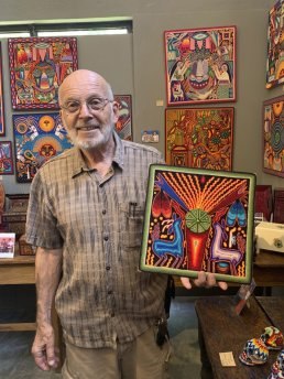 This June 17, 2019 photo shows gallery owner Mayer Shacter holding a Huichol yarn painting, at Galeria Atotonilco near San Miguel de Allende, Mexico. (Emil Varona/Kim Curtis via AP)