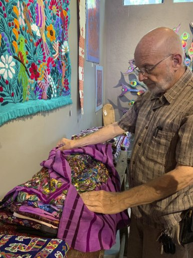 This June 17, 2019 photo shows gallery owner Mayer Shacter holding a hand-embroidered Guatemalan garment, at Galeria Atotonilco near San Miguel de Allende, Mexico. (Emil Varona/Kim Curtis via AP)